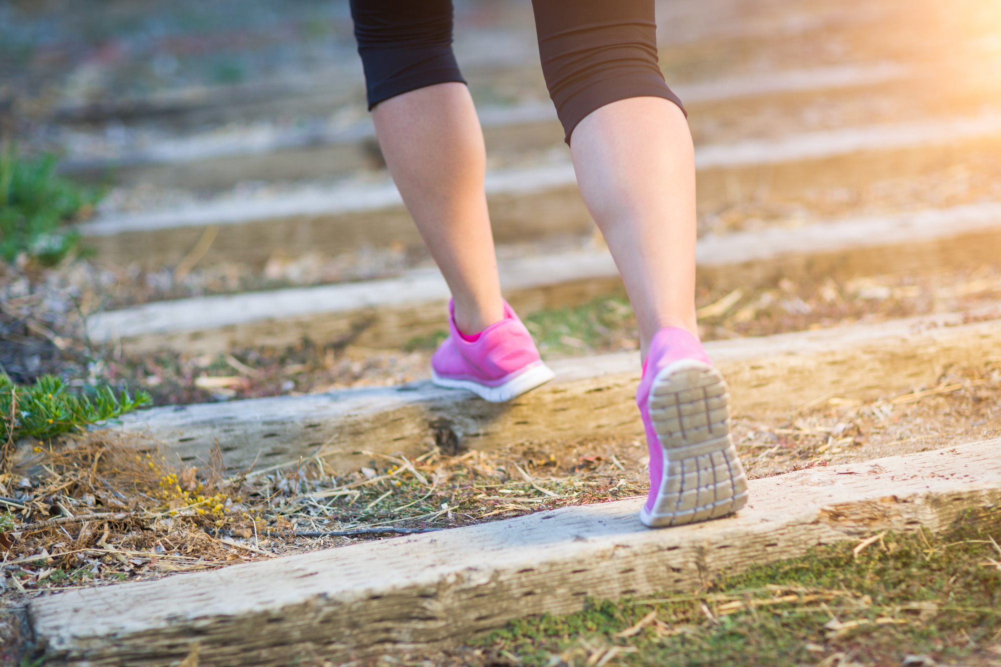 Young Fit Adult Woman Outdoors Walking or Running Up Wooden Steps.
