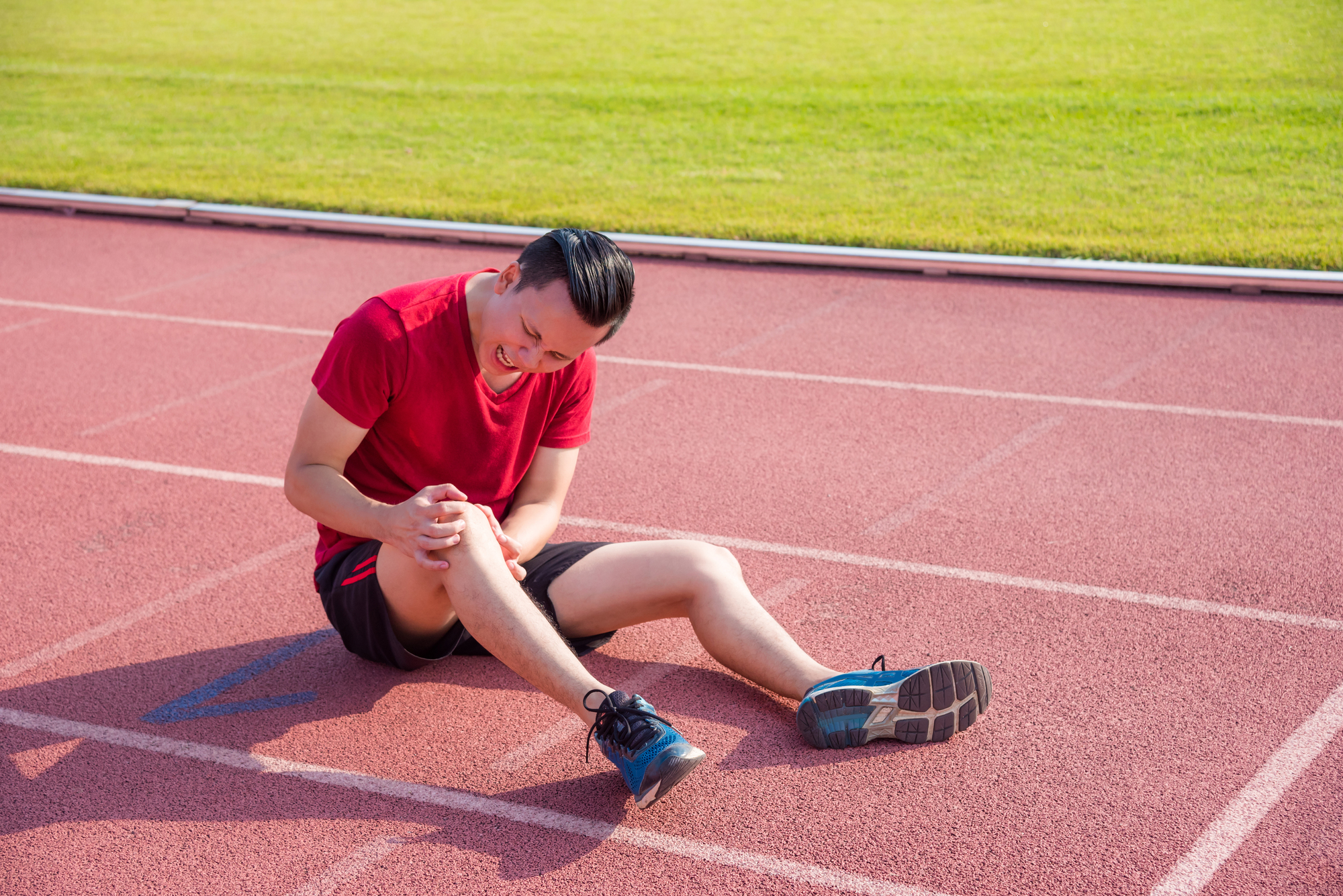 Young asian runner having pain at knee between running in stadiu